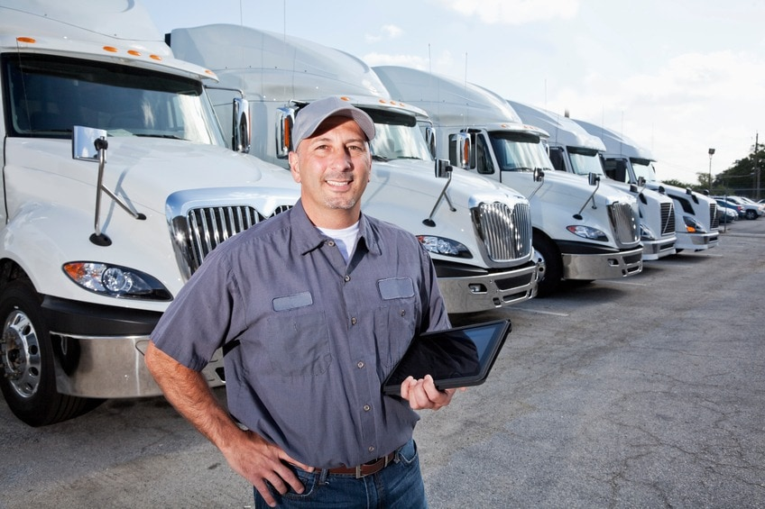 A truck driver is standing in a large parking lot in front of several large trucks. He is facing the camera, and he is wearing a short-sleeved blue shirt, blue jeans, a brown belt and a gray hat. He is holding a black tablet with his left hand. There are six big rigs seen lined up behind him, going from left to right. The large trucks all look the same, being all white and having silver grills and mirrors. There are multiple cars seen parked to the right of the trucks. A cloudy blue sky is seen in the background.